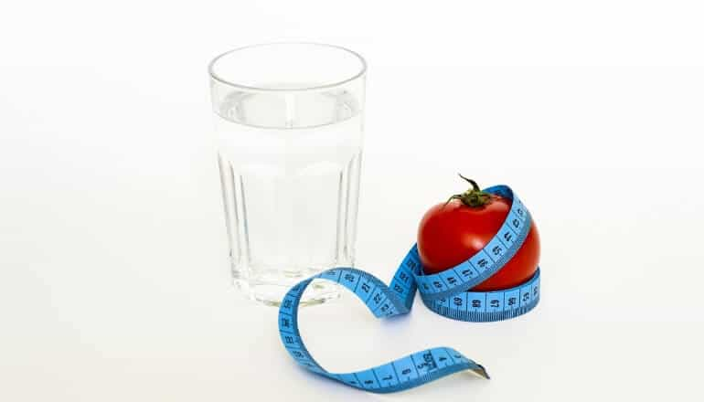 apple and glass of water with a waist tape measure on a table