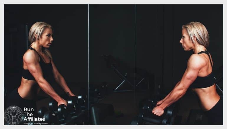 woman bodyvuilding looking in a mirror as she prepares to lift weights