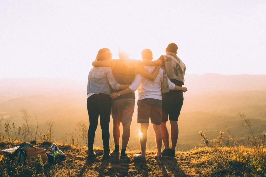 4 people standing on a hill in front of a sunset