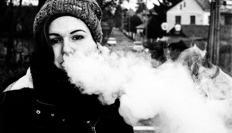 woman blowing vape