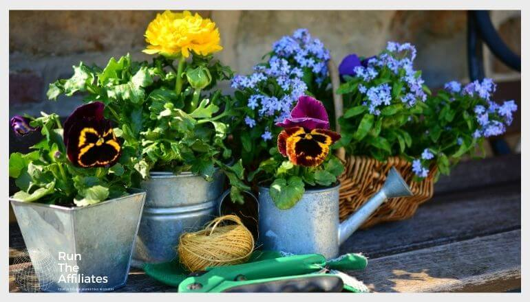 gardening tools and potted flowers on a bench