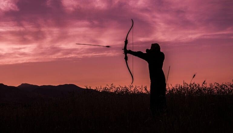 man firing bow