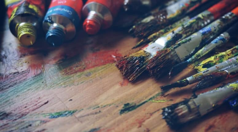 spilled paints and dirty brushes on a wood table