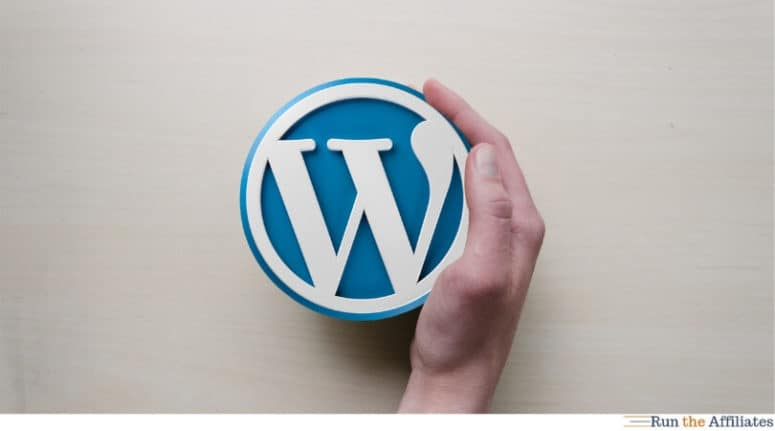 hand pushing a wordpress logo across a table