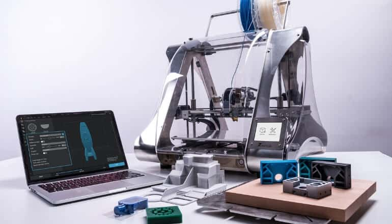 3d printer on table with laptop