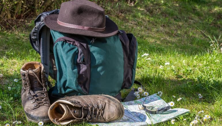 hiking equipment on the ground including a hiking hat