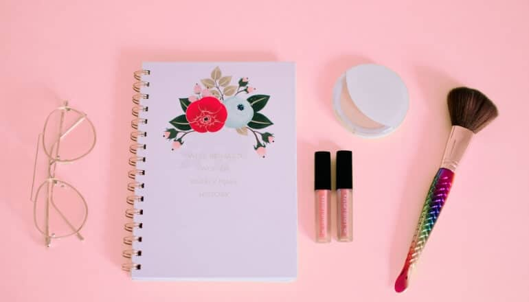 makeup glasses and a notebook on a pink table