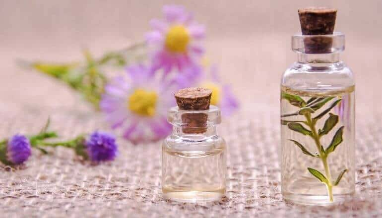 2 essential oils and a variety of flowers laying on a table