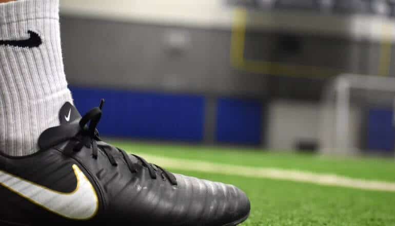 nike branded cleat on a football field