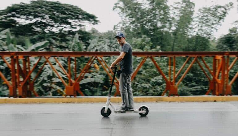 man on scooter in front of guard rail