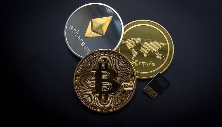 3 crypto coins on a table
