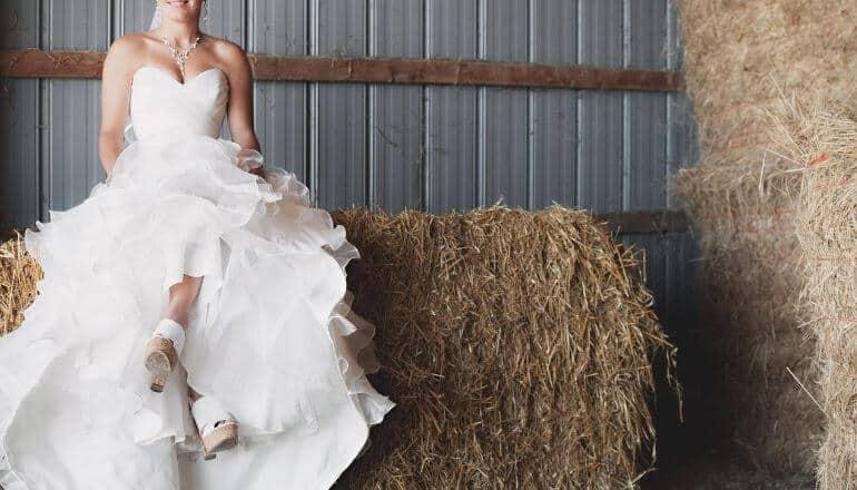 woman in wedding dress sitiing on haybale
