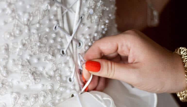 woman tightening string on wedding dress