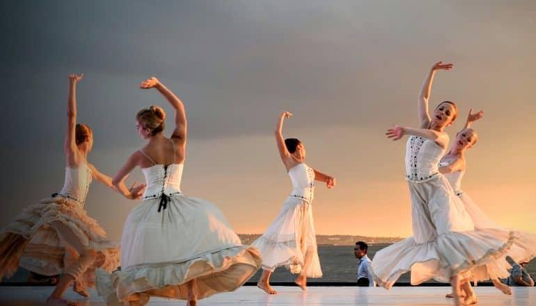 women in white dancing near water