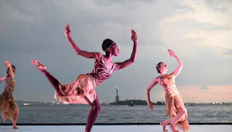 women dancing overlooking statue of liberty