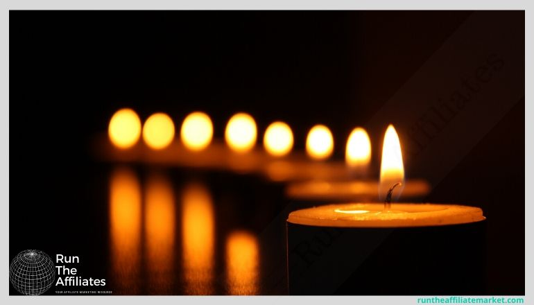 row of lit candles in the dark