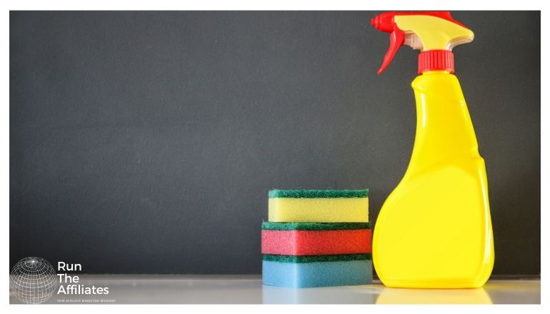 stack of sponges and a yellow spray bottle of cleaner
