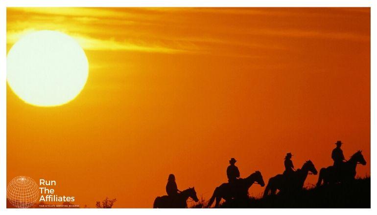 4 riders on horseback at sunset