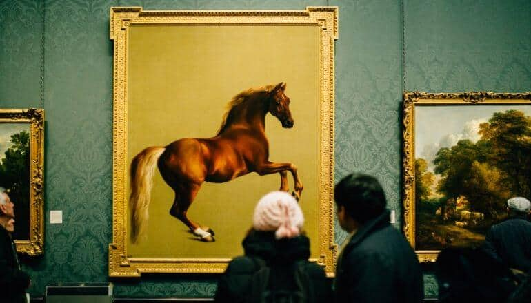 people looking at painting of horse