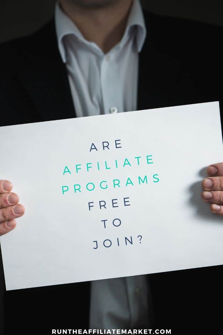 man in black suit and white shirt holding large white card with are affiliate programs free to join written on it.