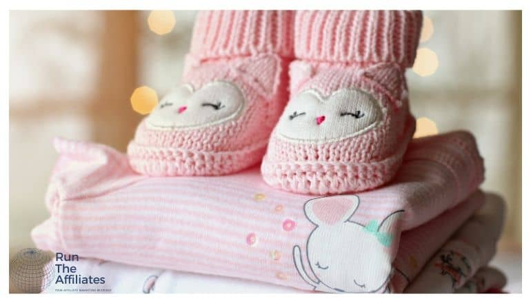 baby clothes in a folded stack with pink knitted boots on top