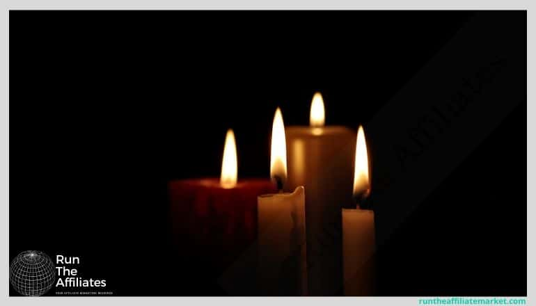 4 lit candles against a black background
