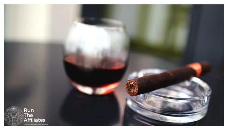 cigar resting on an ashtray next to a glass of brandy
