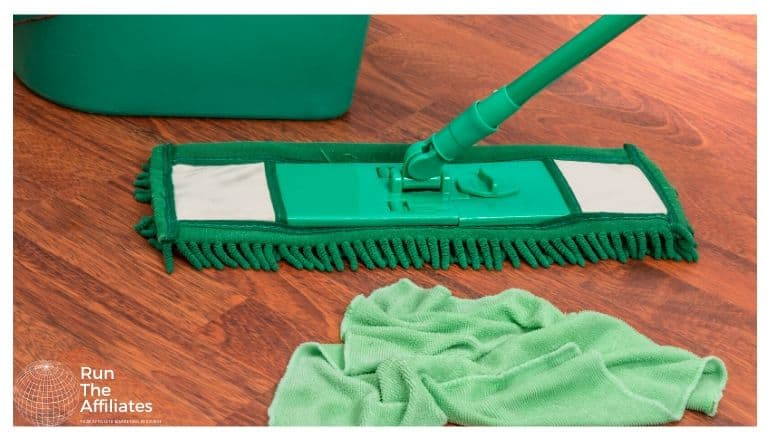 green rag, mop and bucket being used to clean a wood floor