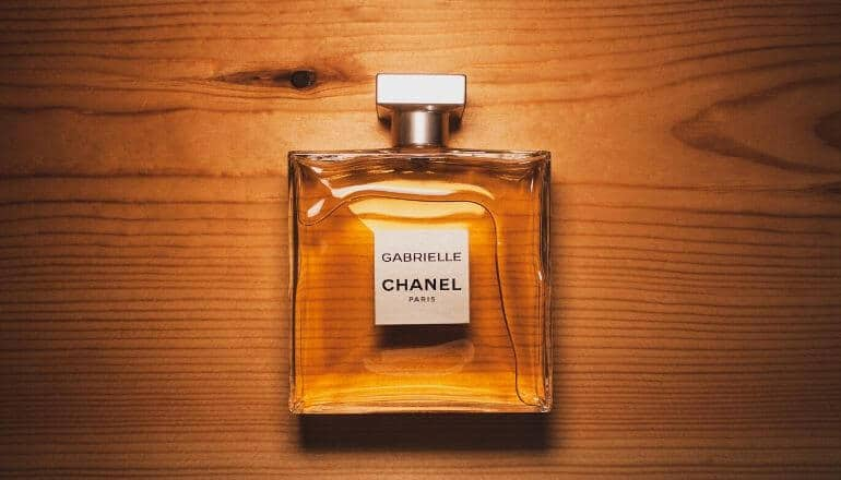 bottle of chanel grabrielle cologne sitting on a wood table, lying flat