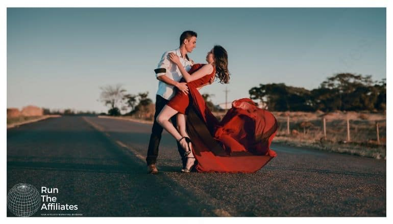 man and women in red dress dancing on a deserted road