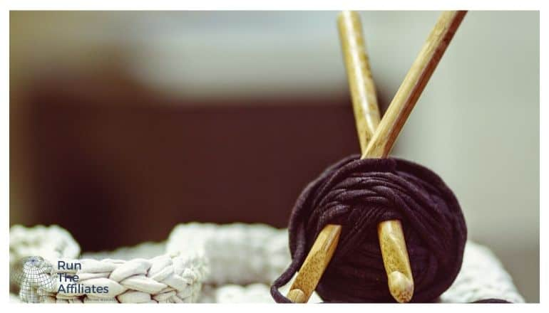 ball of brown yarn with knitting needles sticking into it