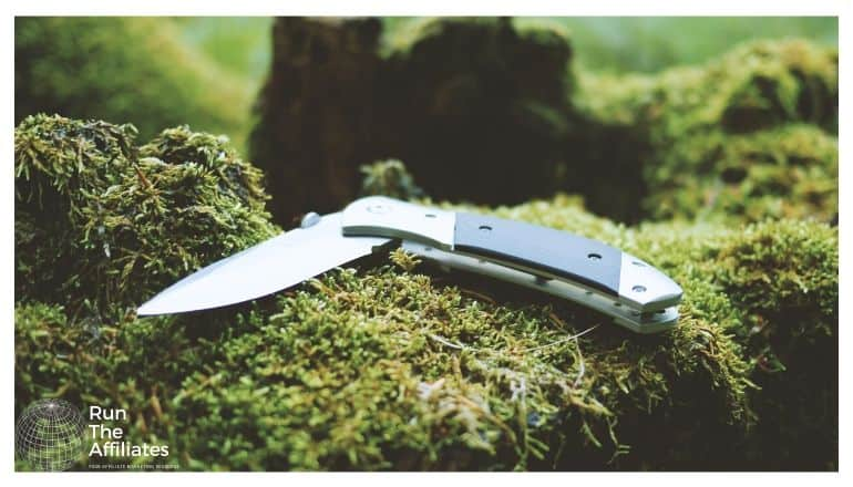 pocket knife resting on a moss covered rock in the forest
