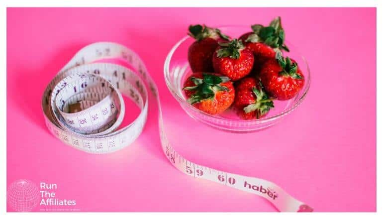 bowl of strawberries next to a waist measure on a pink background