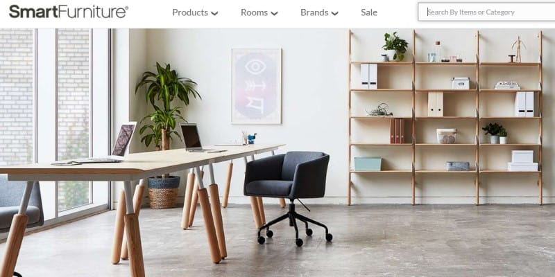 screenshot of the smart furniture website feartuing an office space with a small desk, chair and bookshelf next to a large window