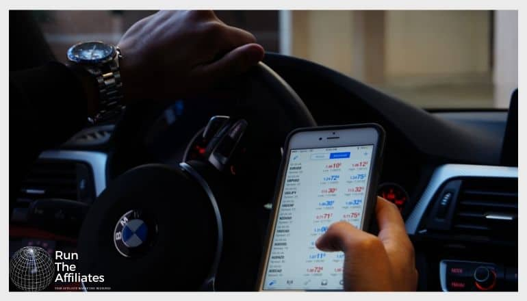 man looking at forex market on smartphone in a car