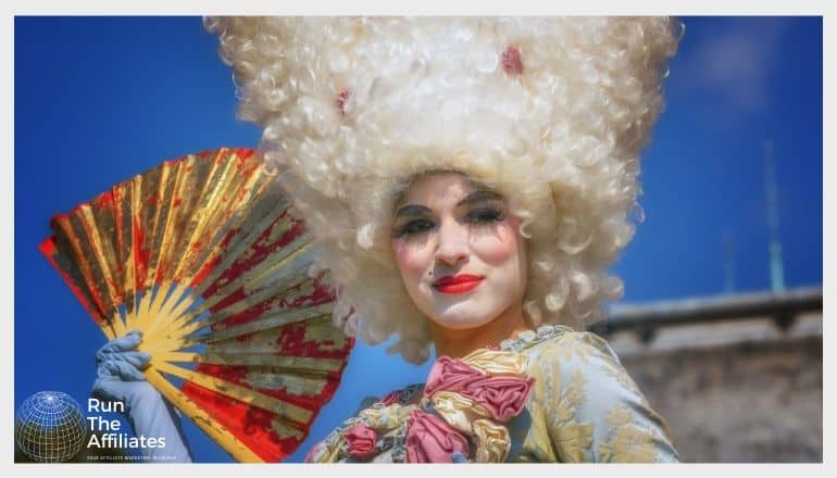 woman in white powder wig fanning herself