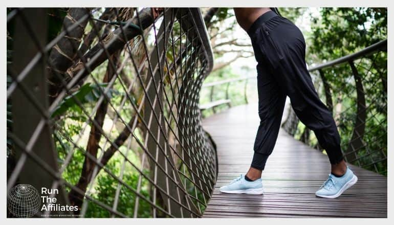 woman in activewear pants leaning on a metal fence on a walway in the forest