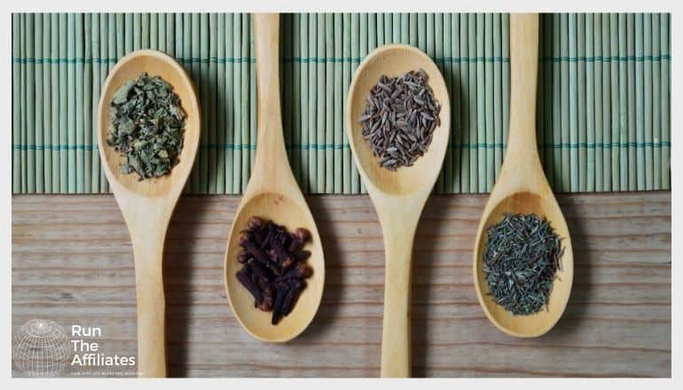 4 wooden spoons with various herbs on them