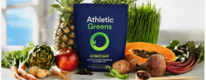athletic greens product with fruit and vegetables displayed behind it