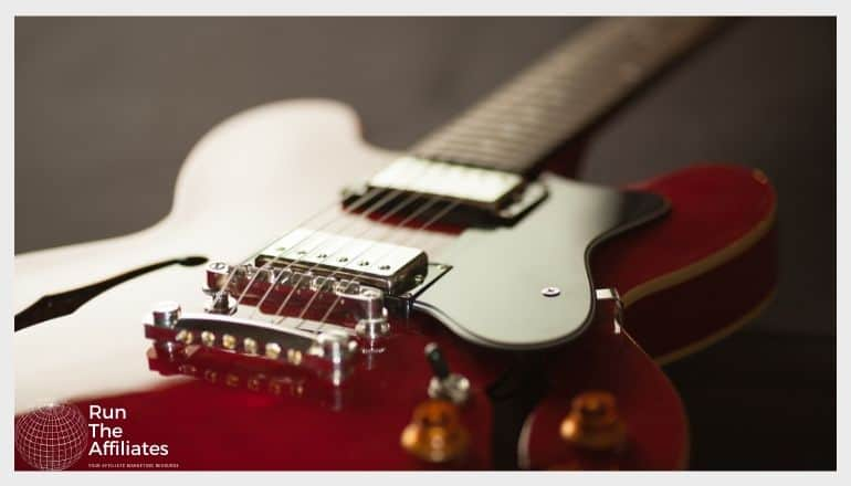 close up image of a rad and gold guitar