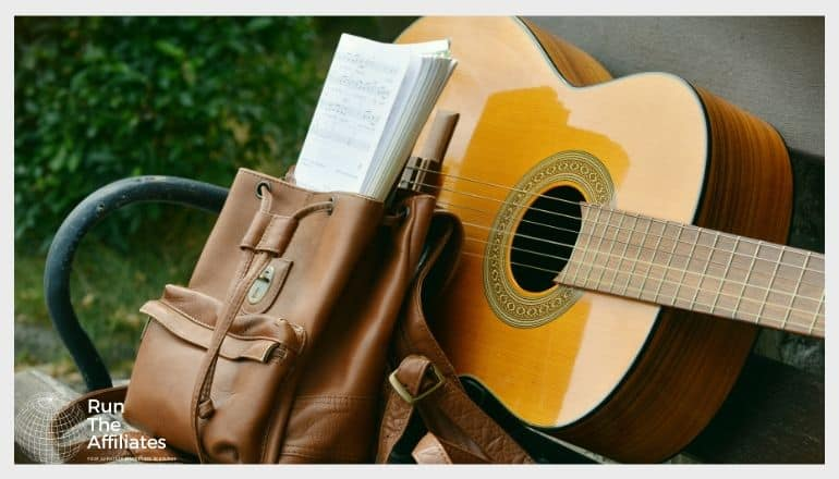 yellow acoustic guitar on a park bench next to a backpack
