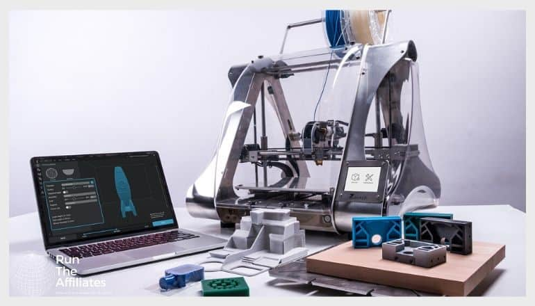 3d printer next to a laptop with a scematic of a blue rocket on the screen