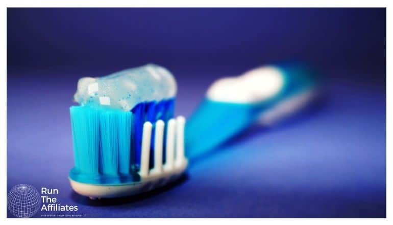 blue and white toothbrush with toothpaste on the bristles setting on a blue countertop