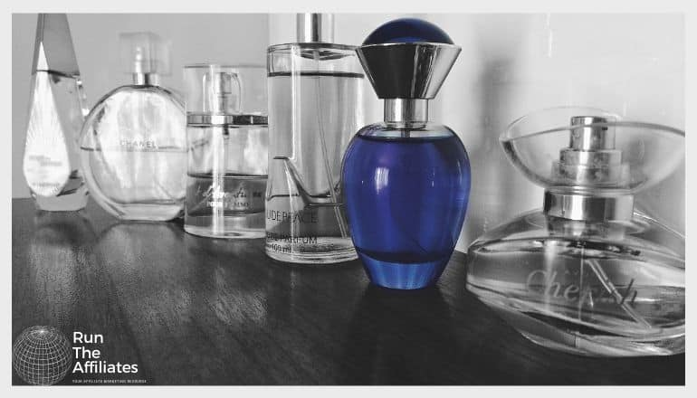 bottles of perfume on a counter in black and white with one bottle a deep blue in contrast