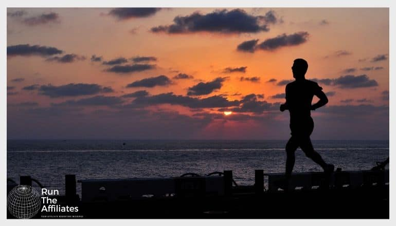 man running on a pier at sunset