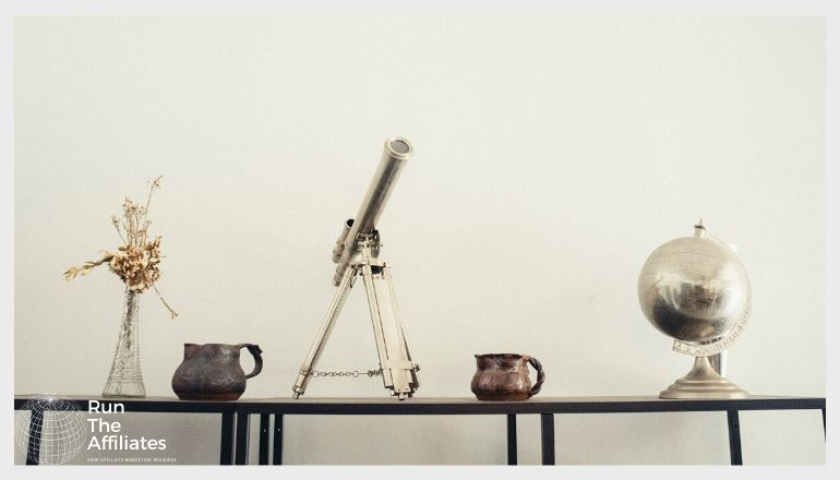 metal telescope and globe on a mantle