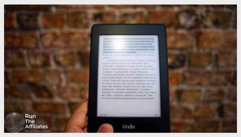 black kindle held in front of a brick wall with an ebook on screen