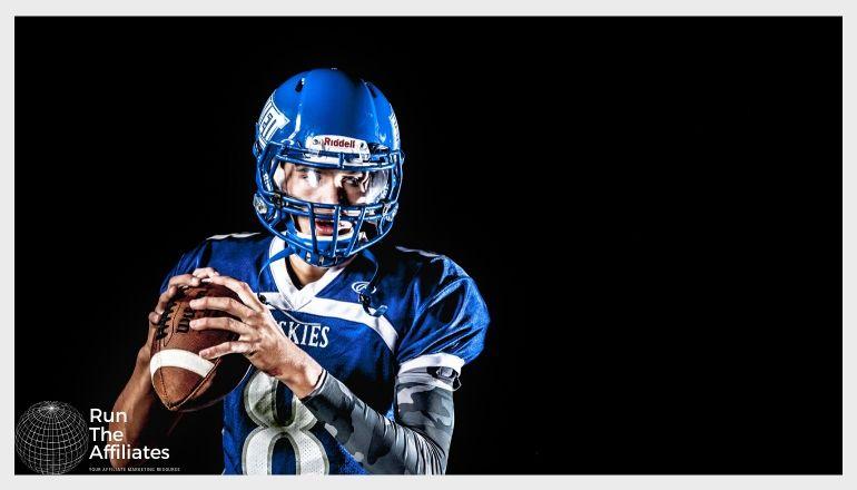 quarterback in blue uniform preparing to throw a pass against a black background