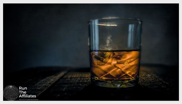 glass of whiskey with ice against a dark background