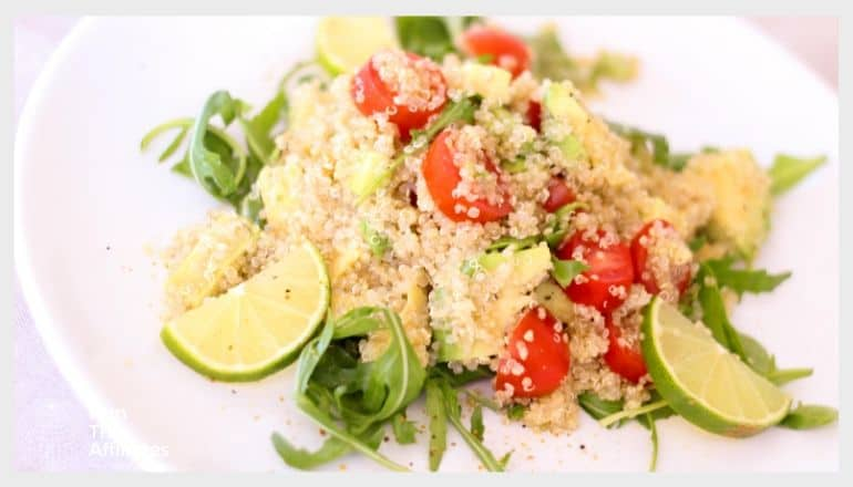 quinoa dish with tomatoes greens and limes served on a white plate